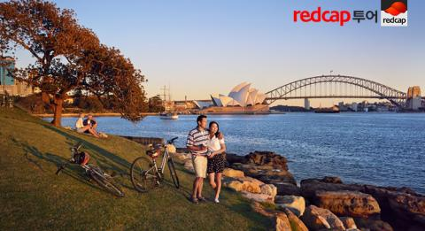 A couple out cycling enjoy a scenic view from Mrs Macquaries Chair, Sydney