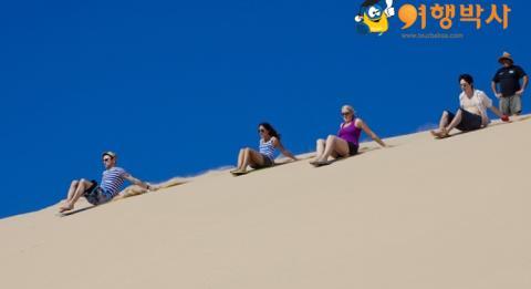 Friends slide down sand dunes at Port Stephens on an ultimate Oz trip.