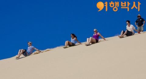 얼티밋 오즈 여행의 포트 스티븐스(Port Stephens)에서 친구들과 사구를 미끄러져 내려오는 모습